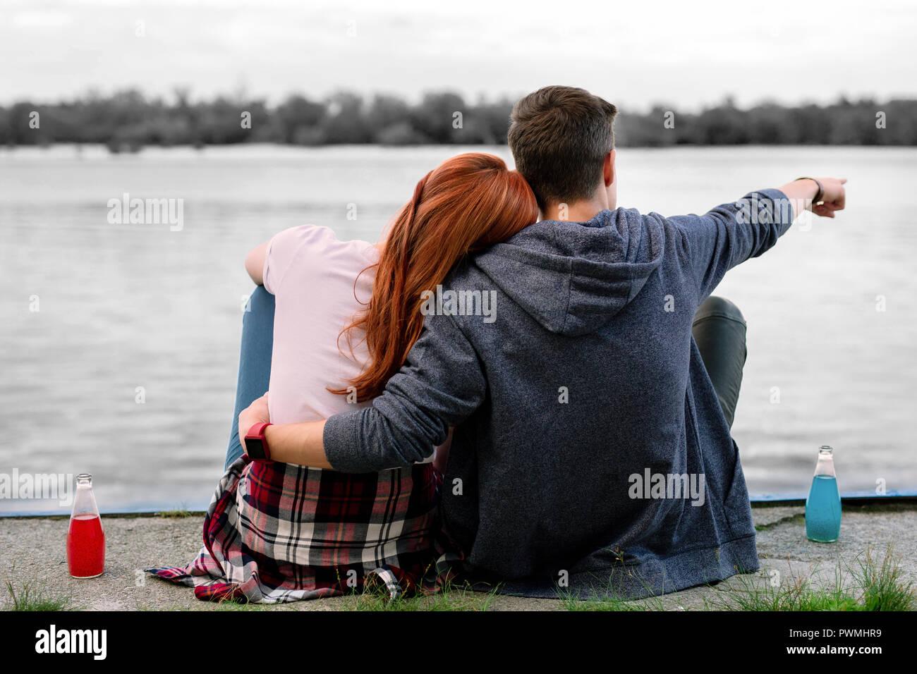 Dark-haired copain serrant sa petite amie assis près de River et de boire de l'alcool Photo Stock