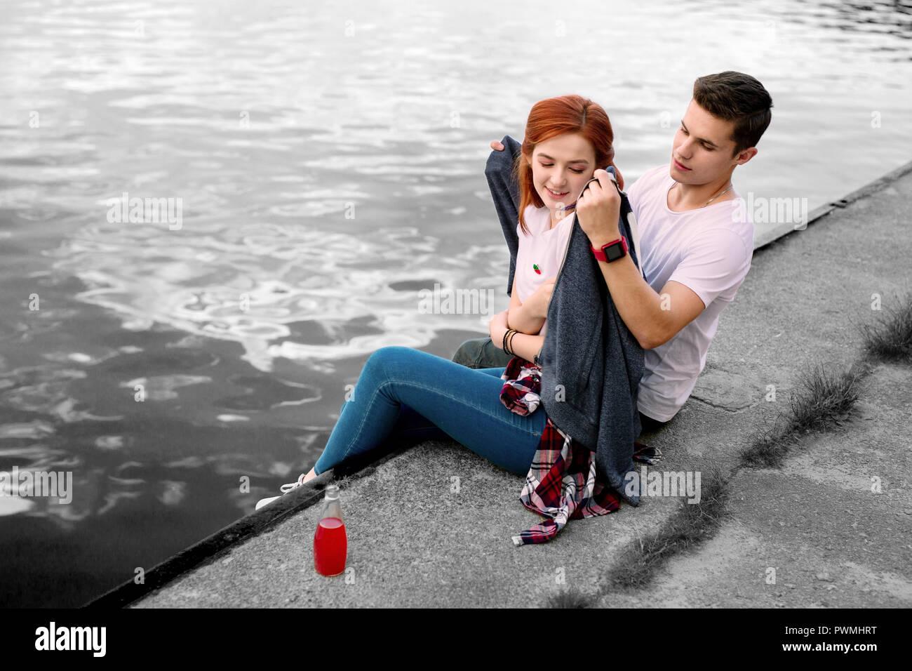 Petit ami aimant prendre soin de donner son veston sport sa petite amie sur soirée froide Photo Stock