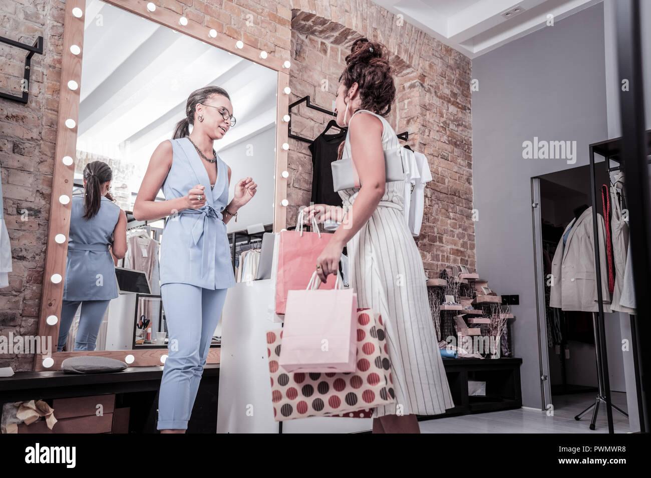 Femme portant robe rayée laissant d'exposition avec de nombreux achats Photo Stock