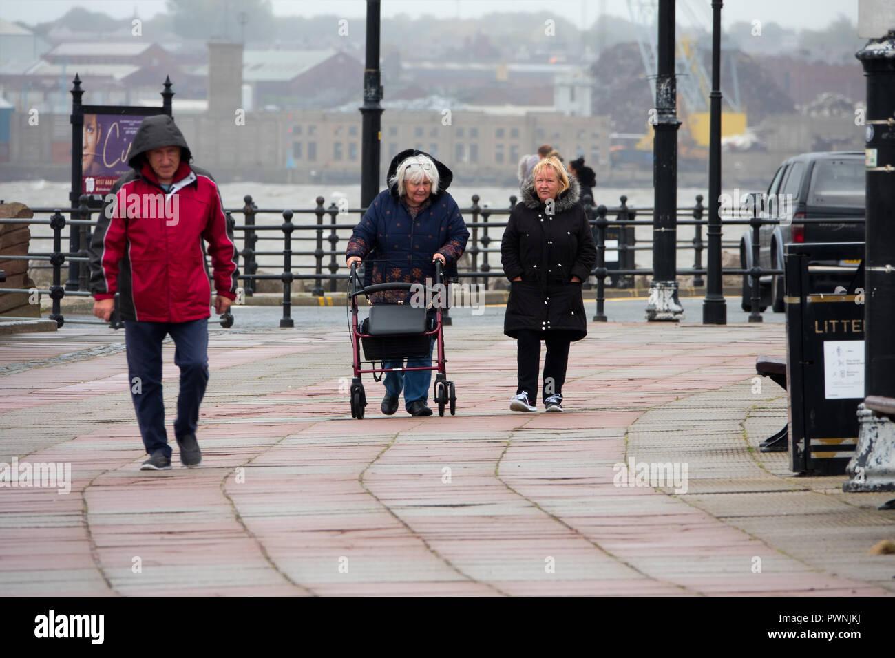 Météo britannique. Une femme marchant le long de la promenade avec une aide à la mobilité en cas de tempête Photo Stock