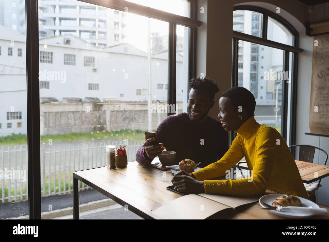 Couple using mobile phone in cafe Banque D'Images