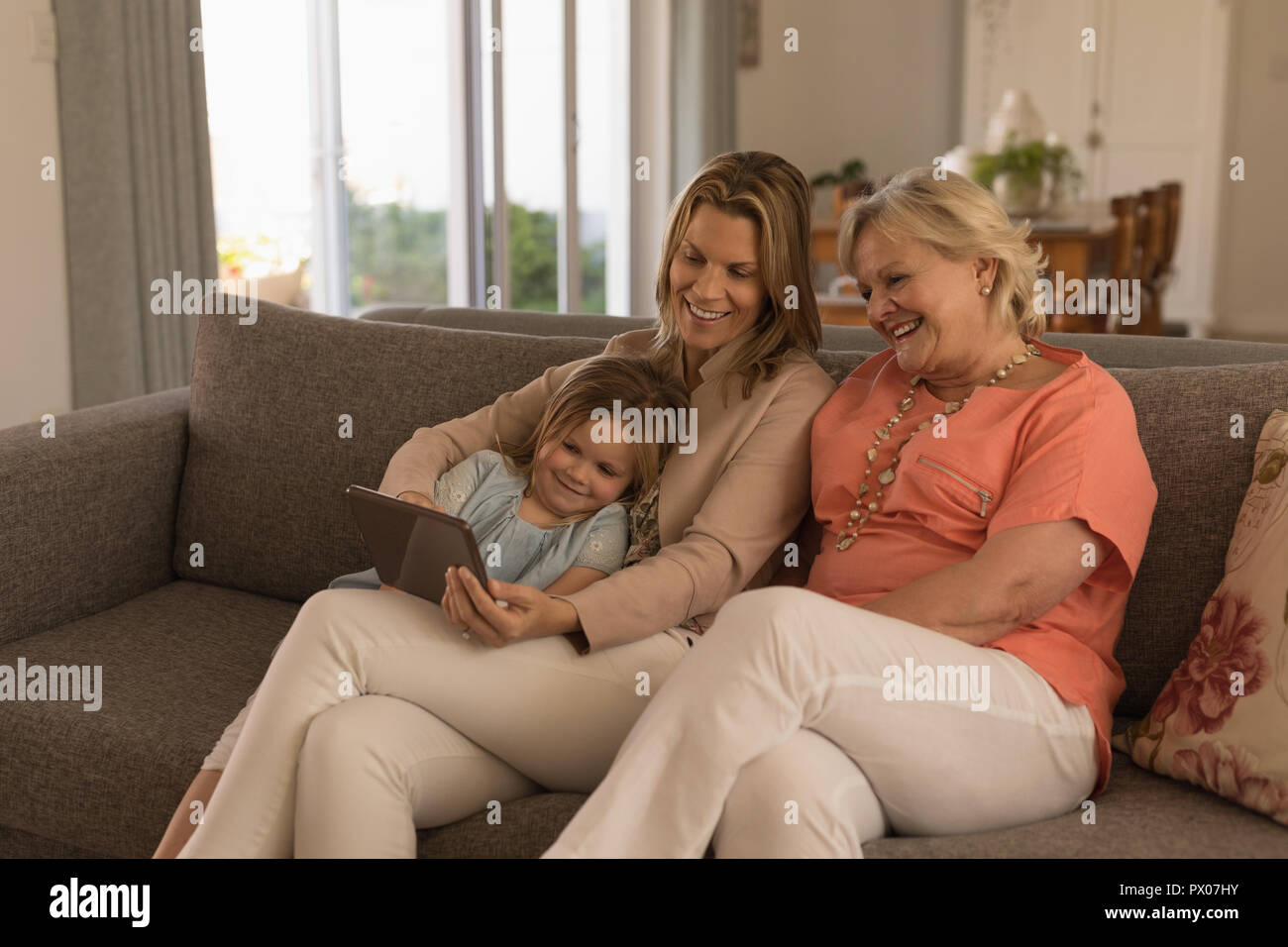 Multi-generation family using digital tablet in living room Banque D'Images