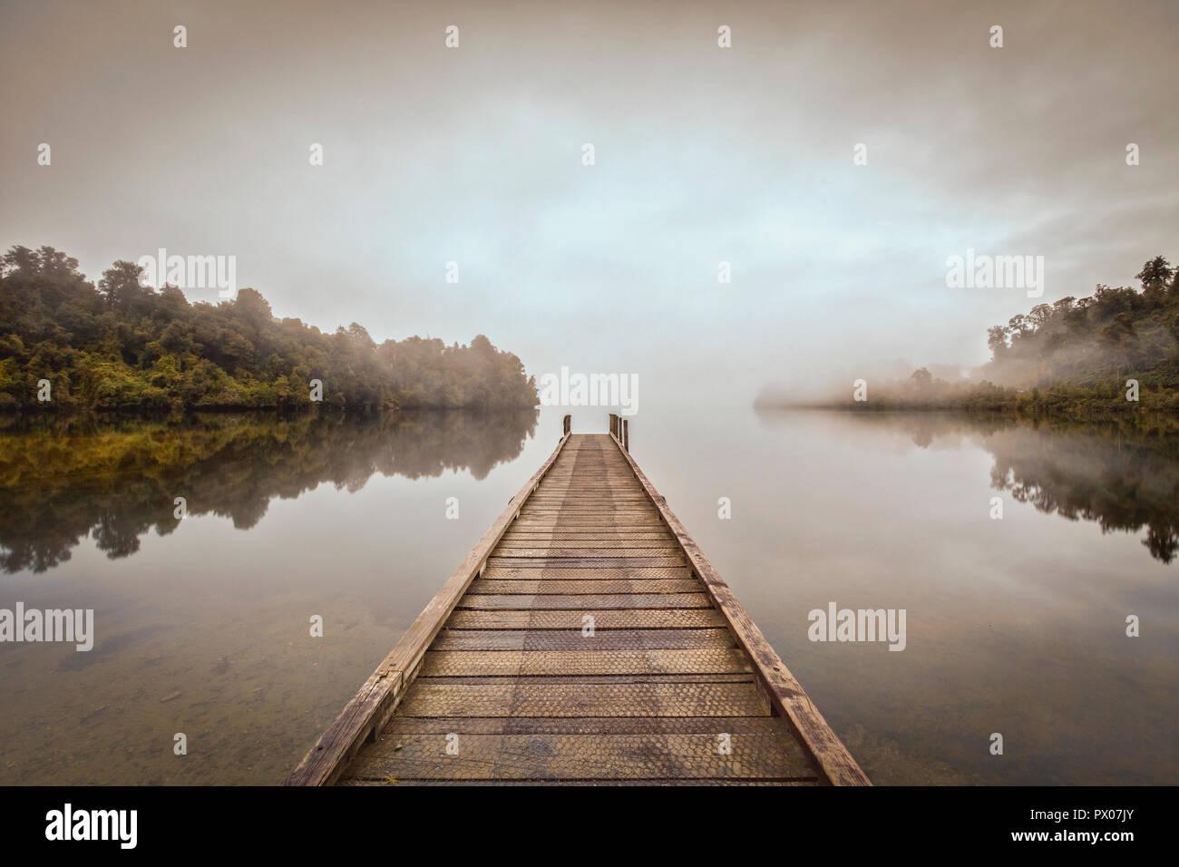 Une jetée sur un lac calme Mapourika, Nouvelle-Zélande, avec l'ensemble de la dérive du brouillard à l'aube. Photo Stock