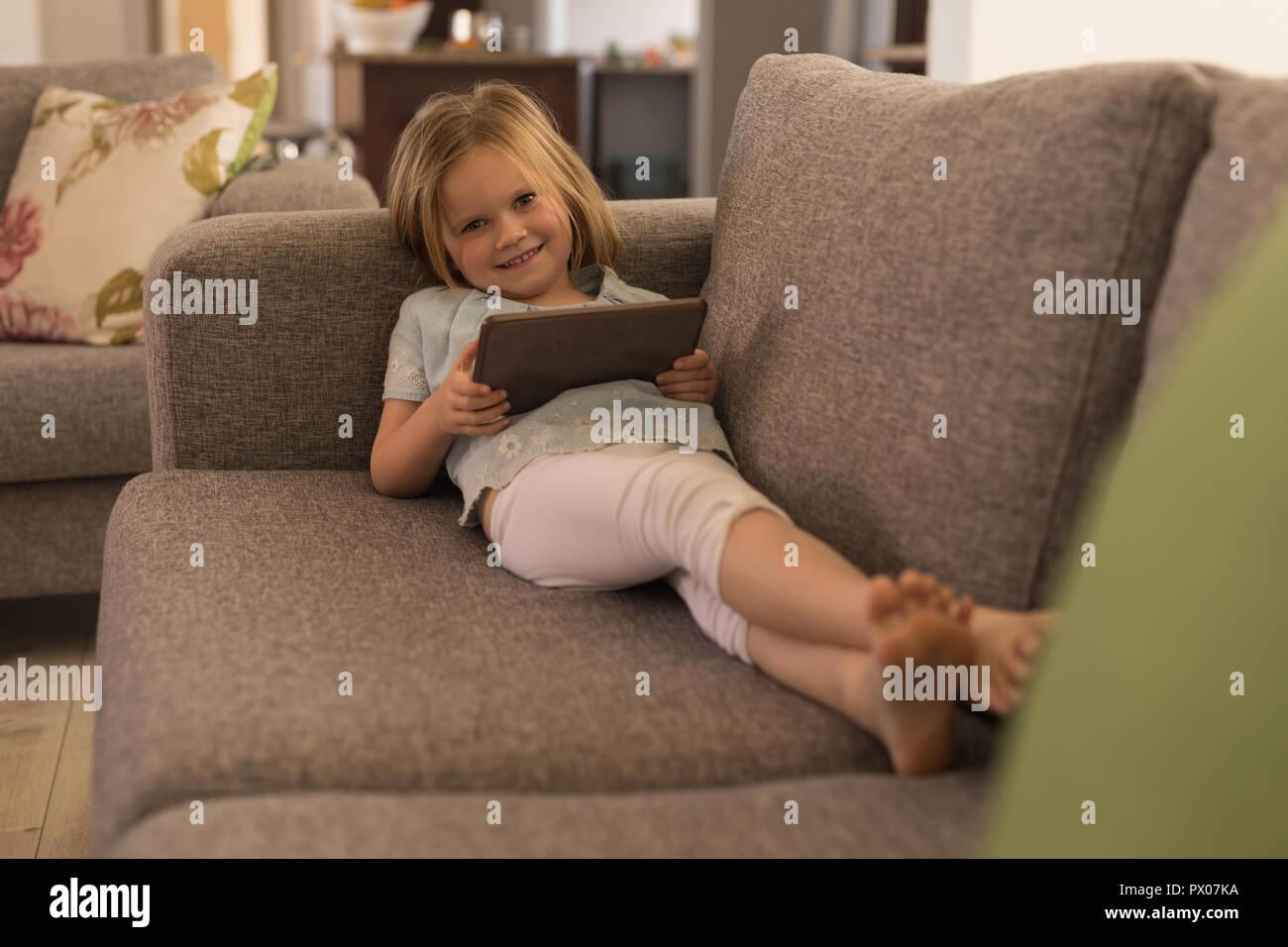 Girl using digital tablet in living room Banque D'Images