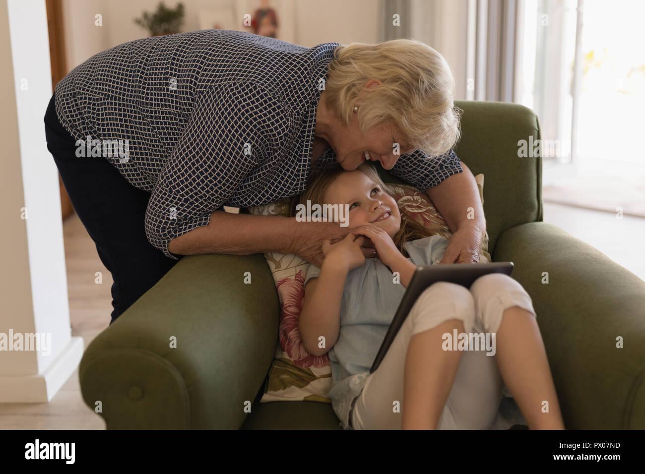 Grand-mère et petite-fille using digital tablet in living room Banque D'Images