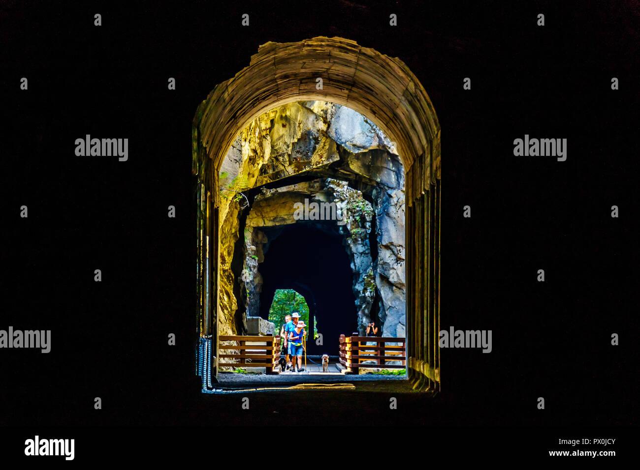 Les touristes marche dans les tunnels d'Othello qui ont été sculptés par la Coquihalla Canyon pour le chemin de fer de Kettle Valley maintenant abandonnée à Hope, C.-B., Canada Banque D'Images