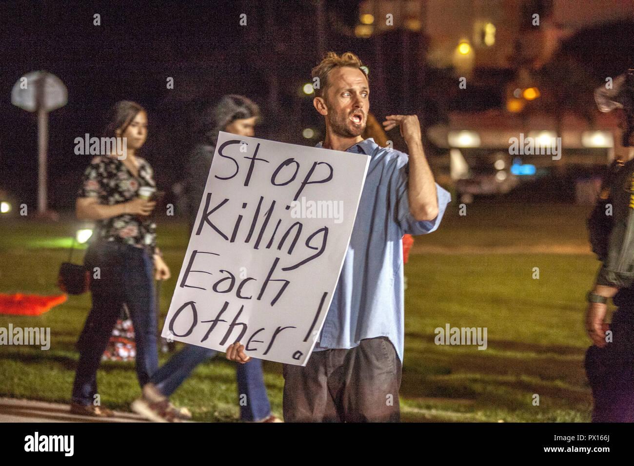 """Portant un panneau disant """"STOP s'entretuer!' un démonstrateur de son message pacifiste cris culturiste à Laguna Beach, CA. Photo Stock"""