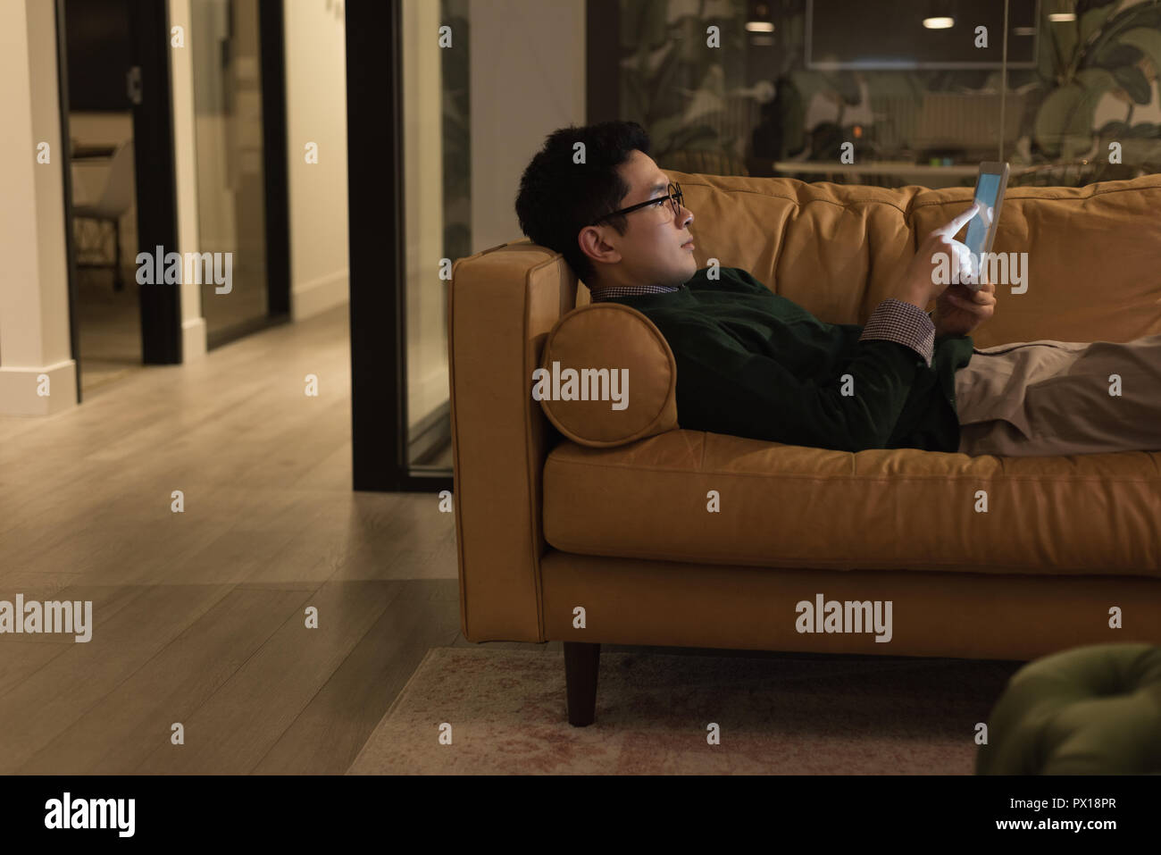 Businessman lying on sofa and using digital tablet Banque D'Images