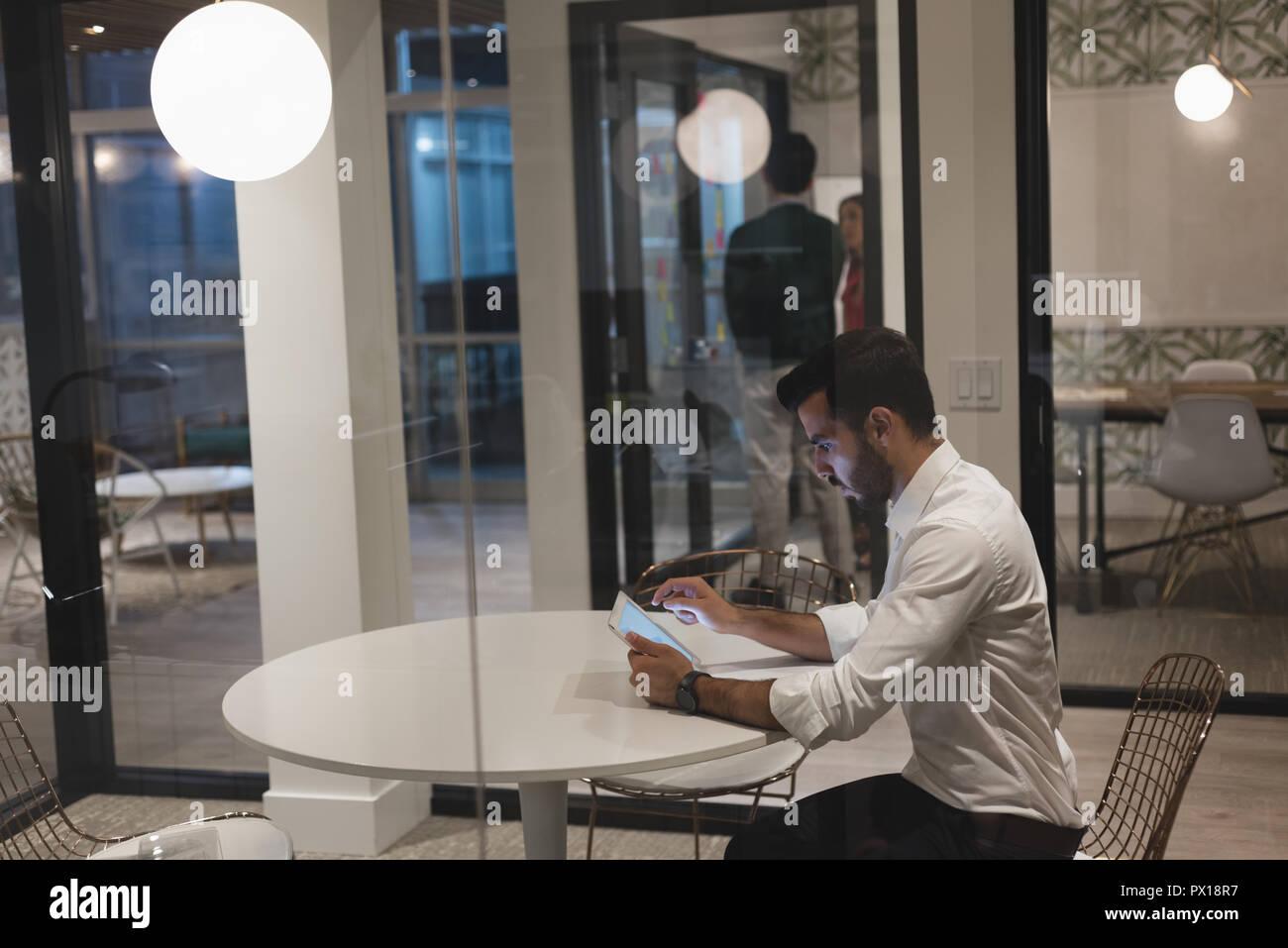 Businessman using digital tablet in office à la cabine Banque D'Images