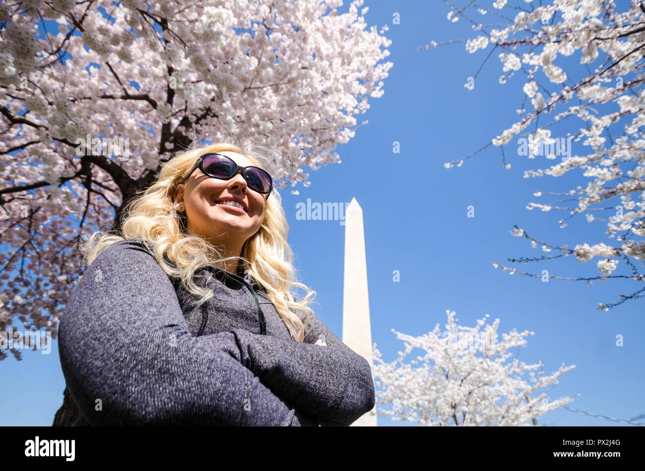 Femme blonde pose avec un sentiment de réalisation et d'accomplissement près du Monument de Washington avec des cerisiers en fleurs Photo Stock