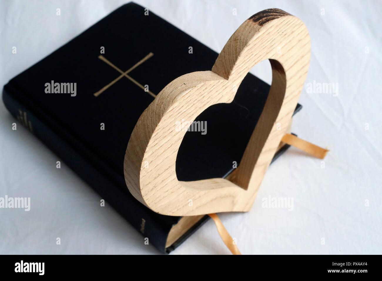 Coeur en bois sculpté sur une Bible. Photo Stock