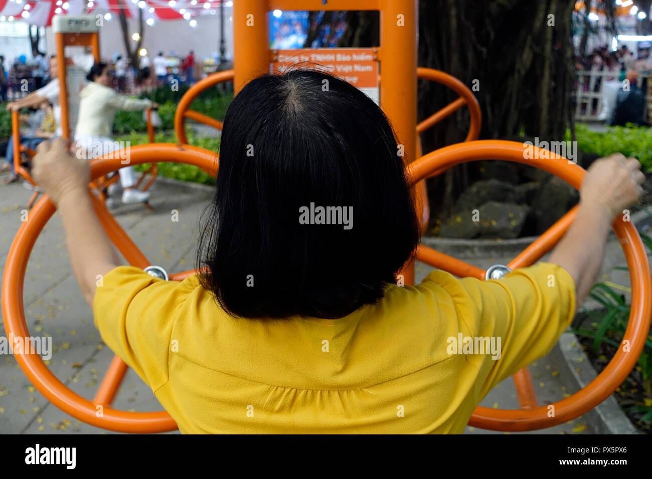 Une femme d'âge moyen à l'aide de l'équipement d'exercice dans un parc. Ho Chi Minh Ville. Le Vietnam. Photo Stock