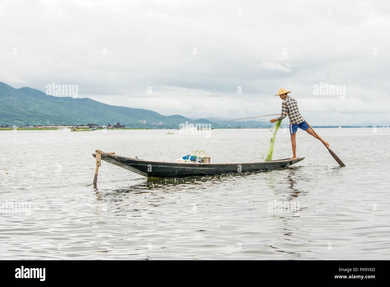 Transport local Les jeunes hommes portant des pêcheurs birmans, à l'aide de bâton et net pour le poisson, en équilibre sur un pied sur le bateau, le lac Inle au Myanmar, Birmanie Banque D'Images