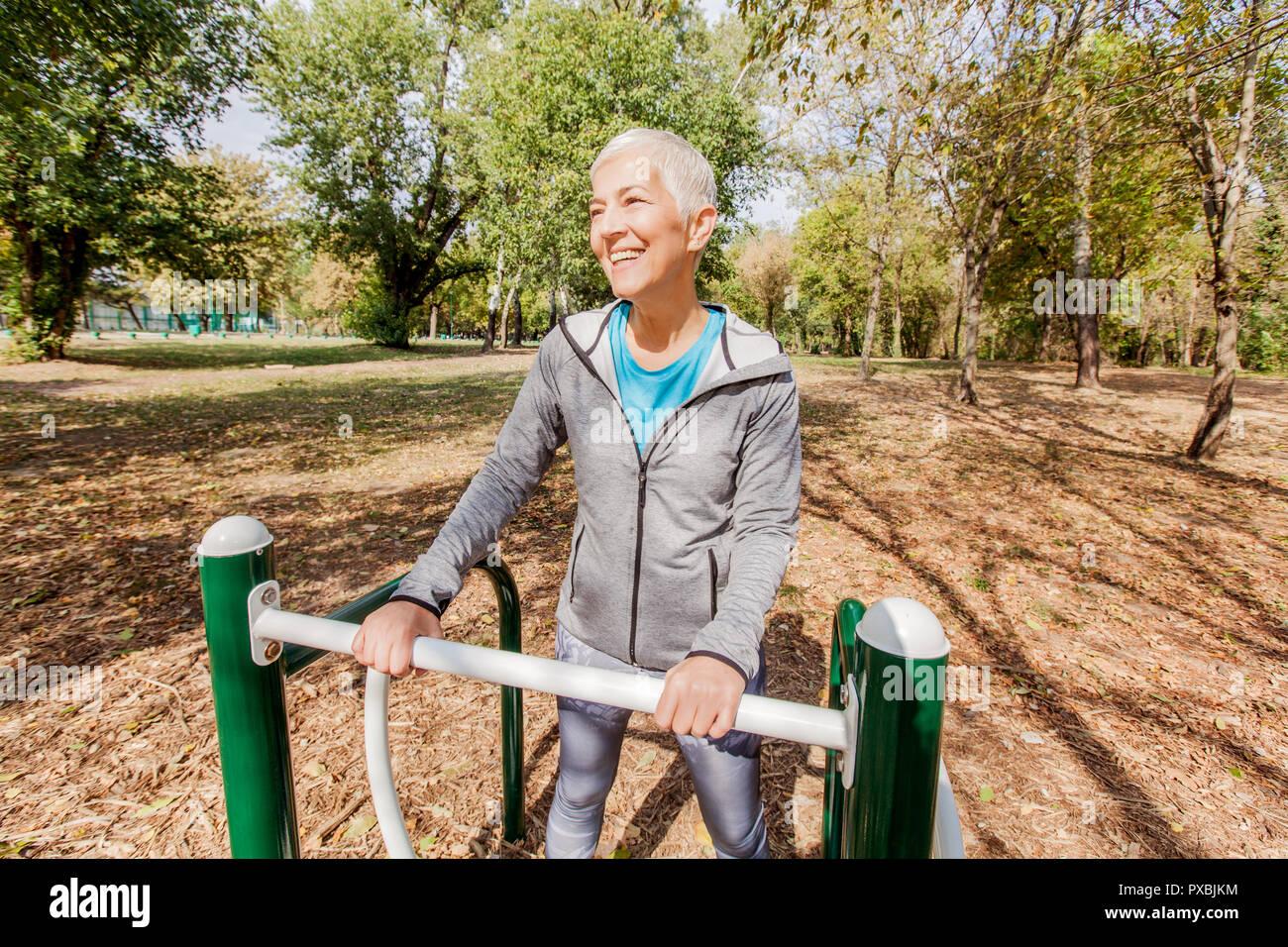 Vieille Femme dans l'exercice de sports de vêtements de plein air au parc de remise en forme, les modes de vie des personnes mûres. Banque D'Images