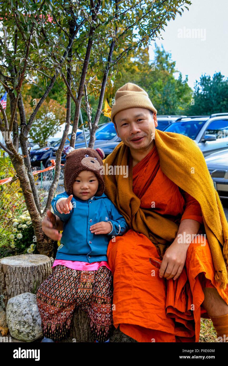 Un moine bouddhiste thaïlandais frisquet a célébré la fin du carême posant avec un enfant thaïlandais au Wat Bouddha Temple Vararam Boston. C'est l'un des deux seuls temples bouddhistes dans le Massachusetts. Photo Stock