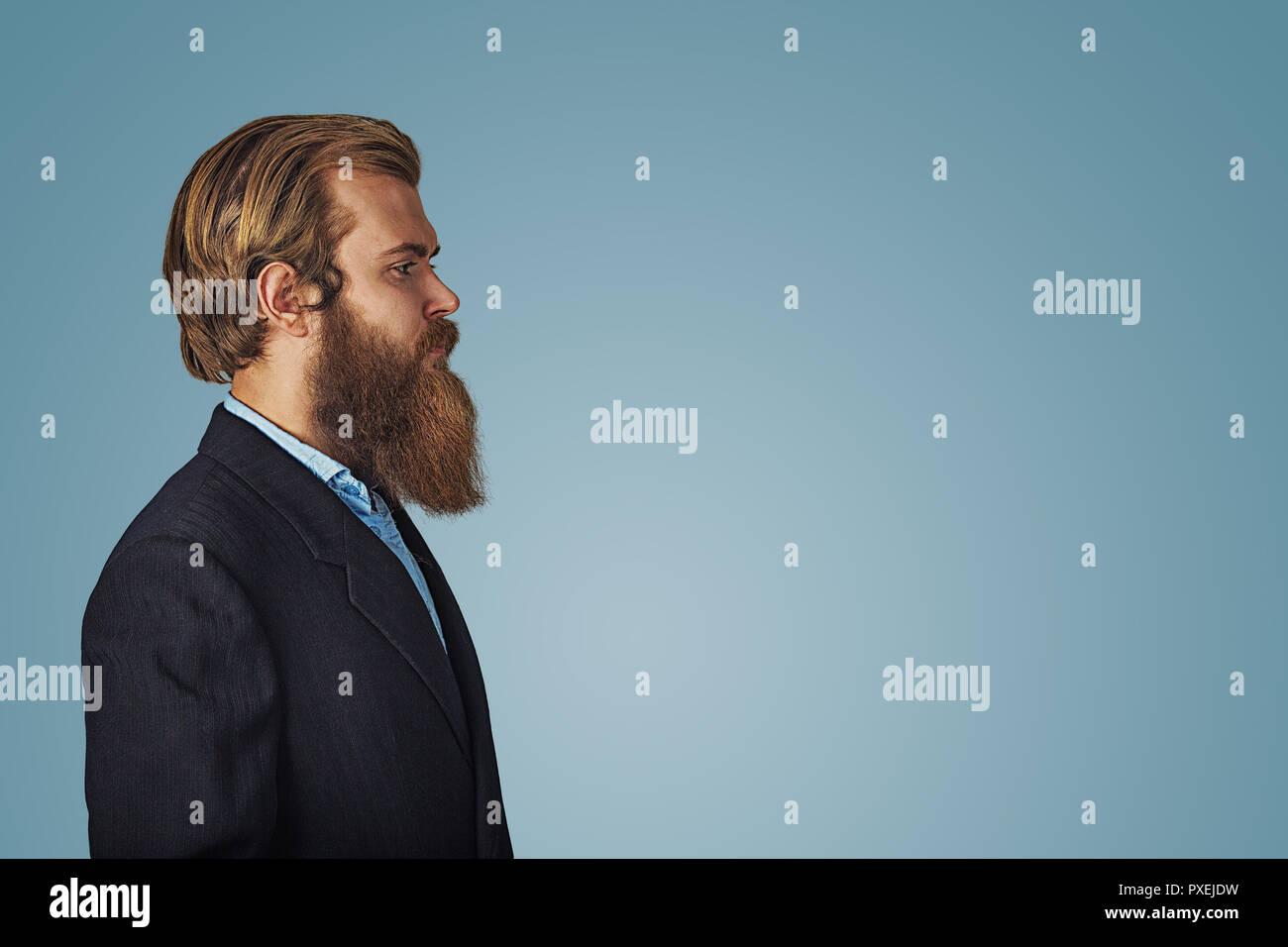 Vue latérale de la mode portrait grave hipster barbu bel homme en costume  noir et chemise bleue isolé sur fond bleu. Négatif express cf025371b27