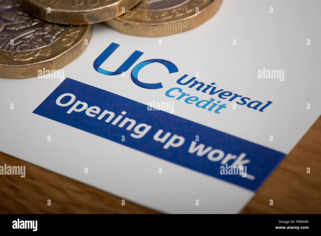 Un morceau de papier avec le logo crédit universel, repose sur une table avec quelques pièces de 1 €. Photo Stock