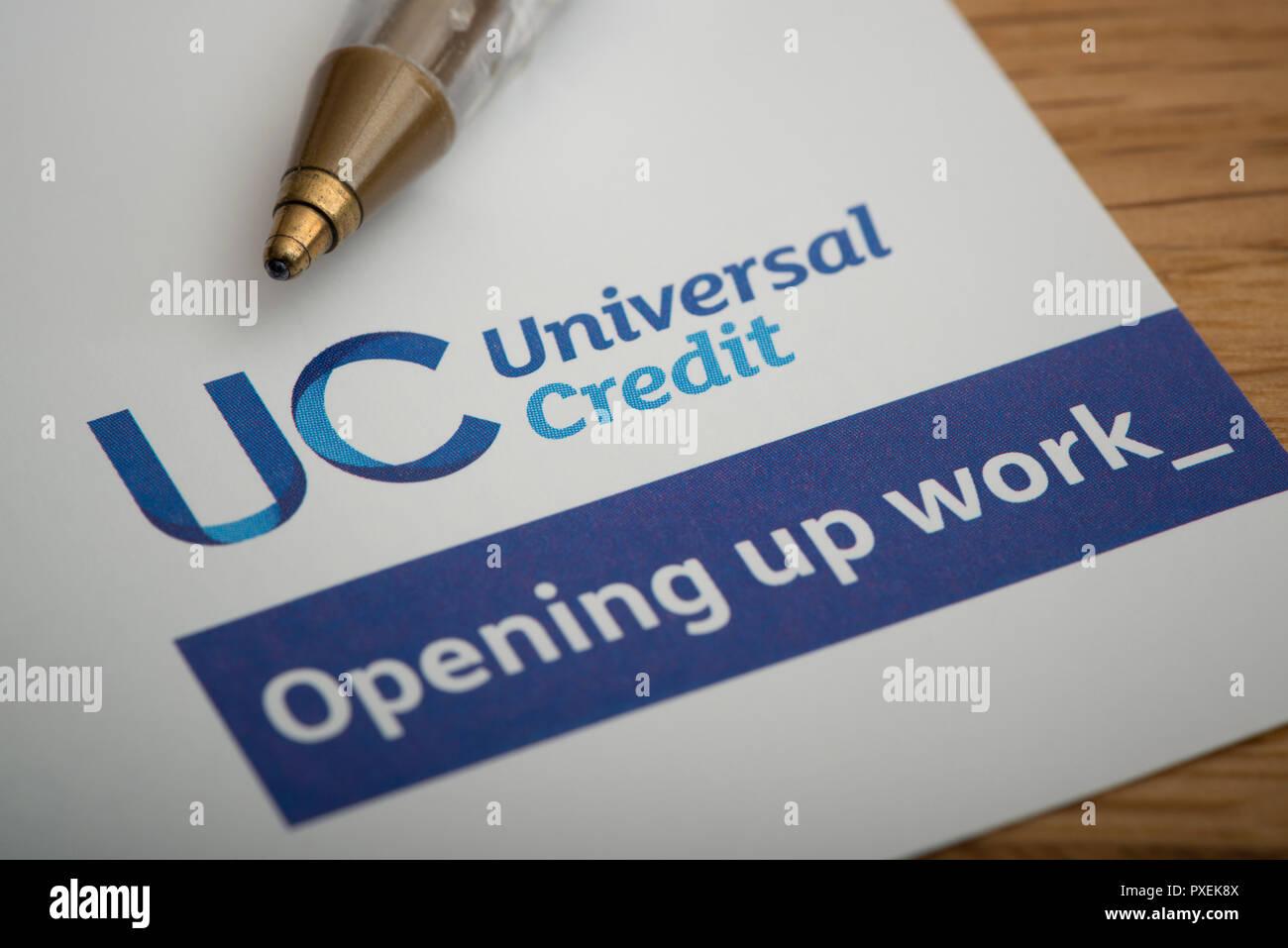 Un morceau de papier avec le logo crédit universel, repose sur une table avec un stylo. Photo Stock