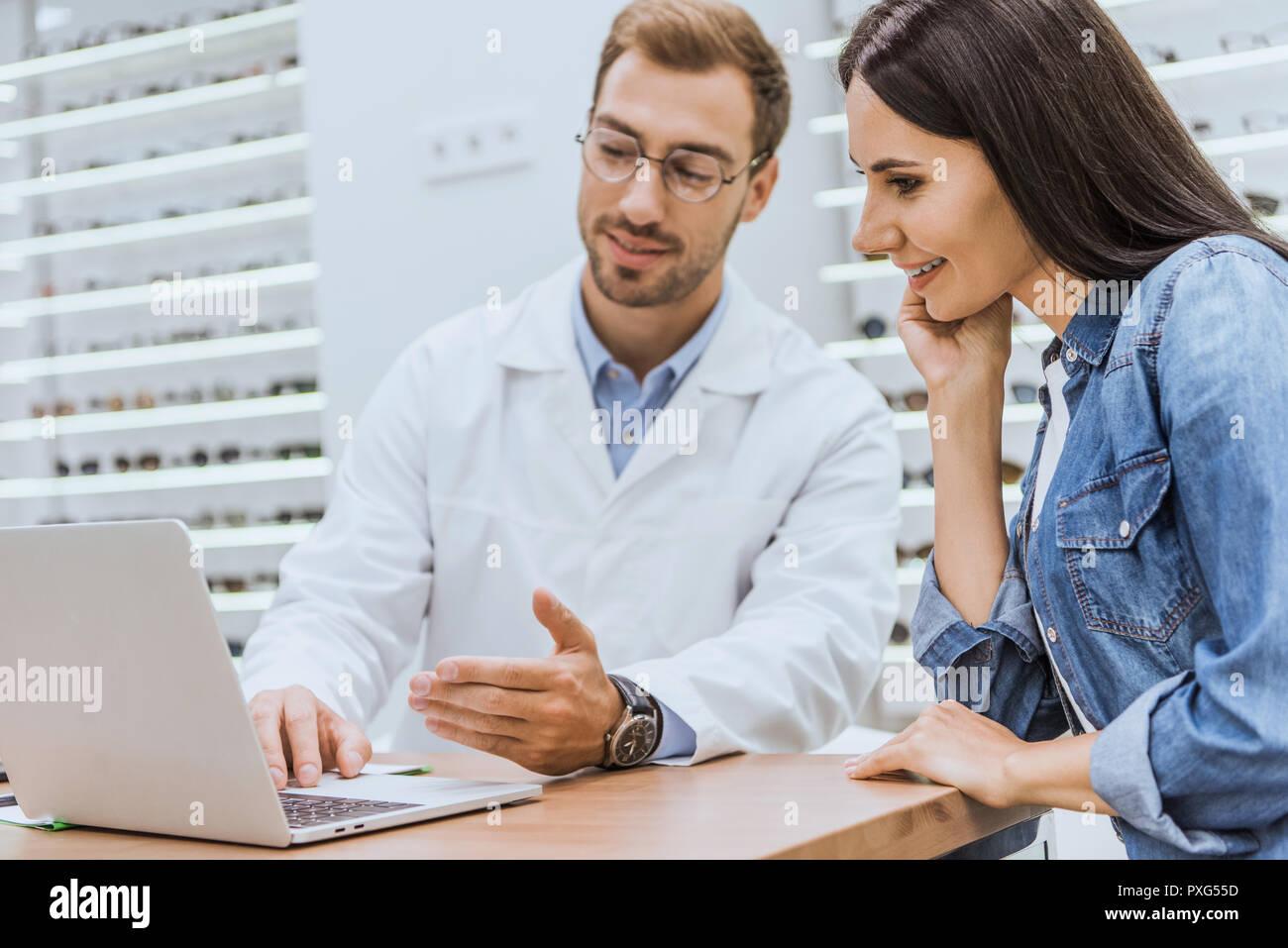 Smiling woman standing près de l oculiste mâle pendant qu il fait à la main  à l écran de l ordinateur portable en optique 6bc5f3450aa3