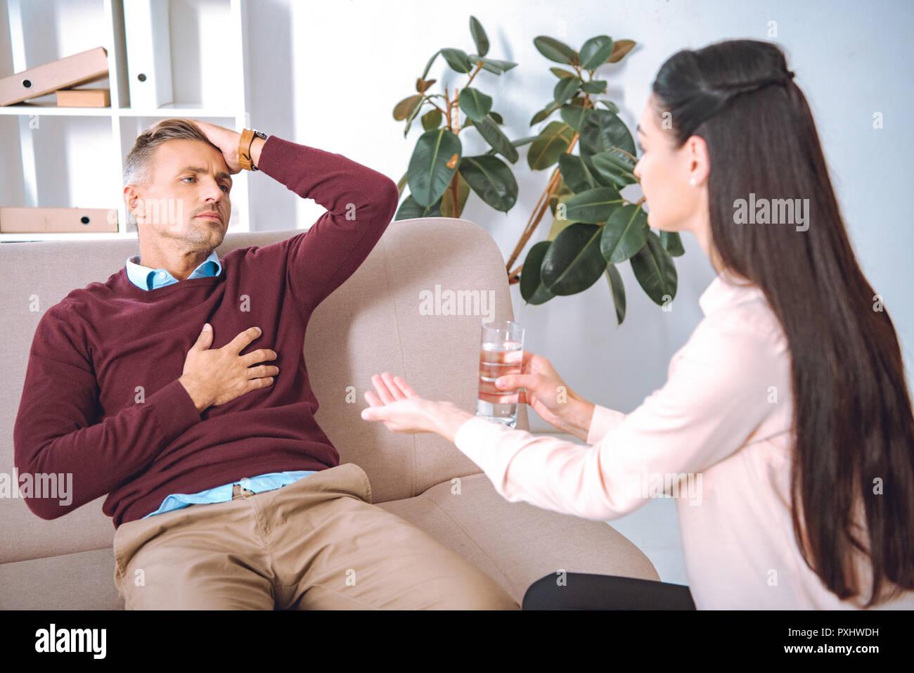 Psychothérapeute en donnant de l'eau et comprimé au patient avec le chagrin Photo Stock