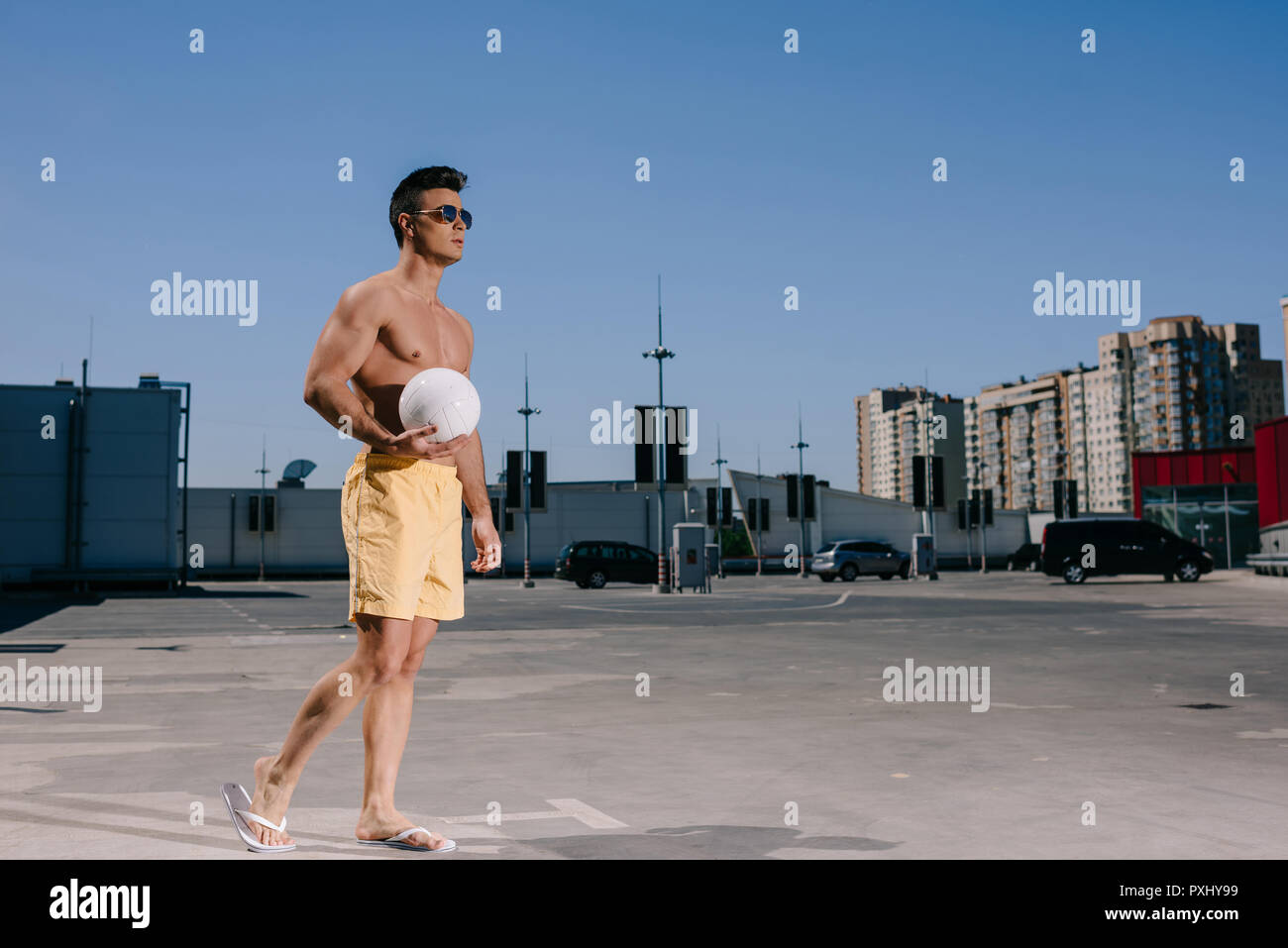 L'homme torse nu avec le volley-ball ball le parking gratuit Photo Stock