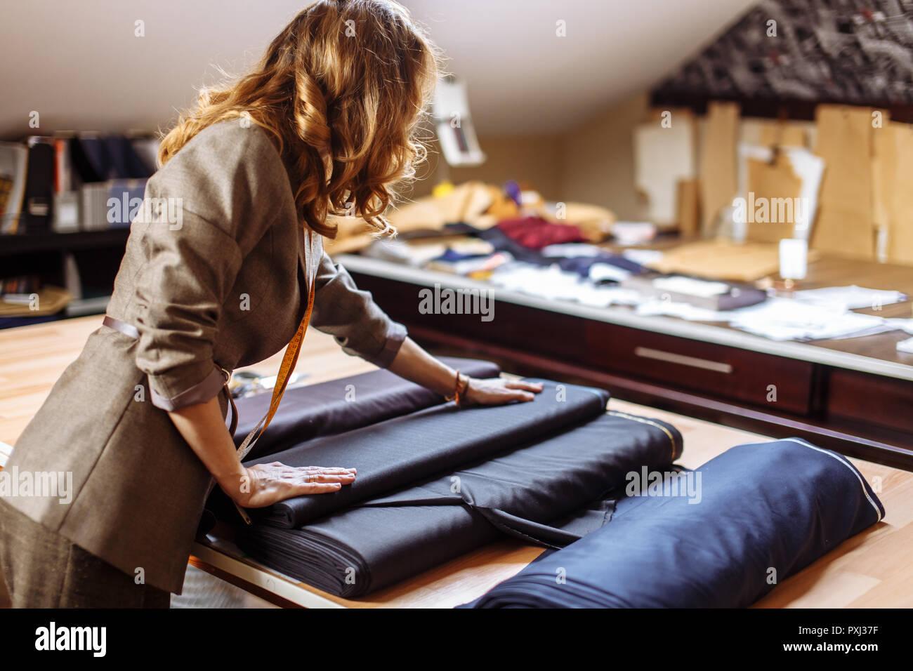 Designer de mode féminine travaillant sur tissu habillent avec accessoires de couture sur la table Photo Stock