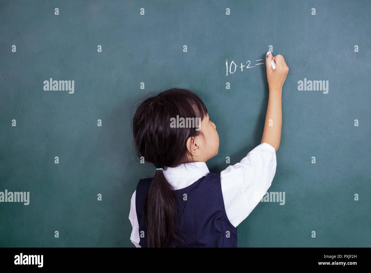 Chinois asiatique petite fille écrit sur tableau noir dans la salle de classe Photo Stock