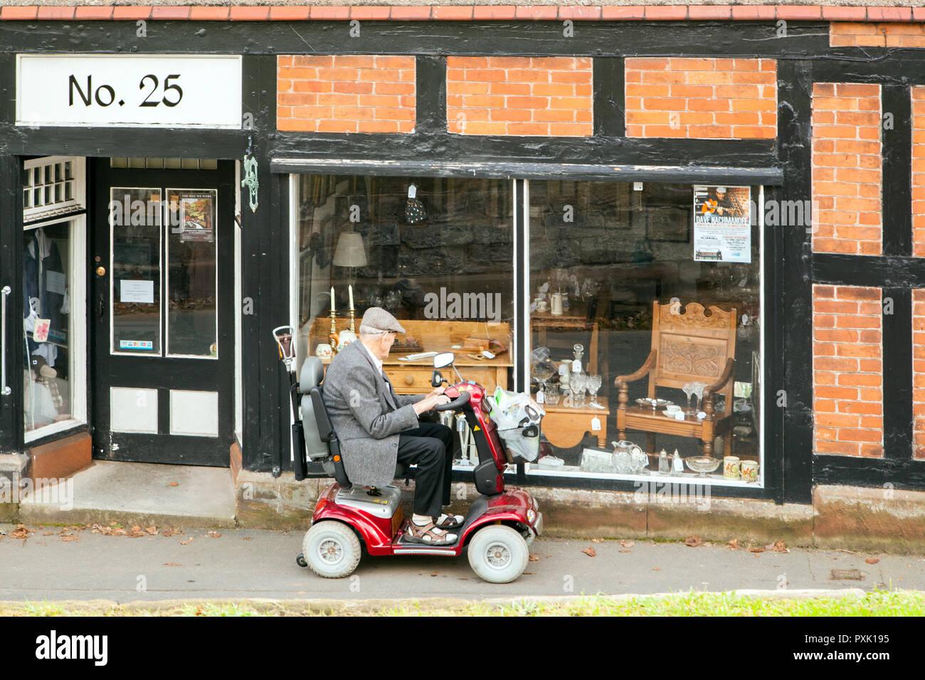 Vieil homme âgé personne sur un scooter de mobilité arrêté pour regarder dans la fenêtre d'un magasin d'antiquités Photo Stock