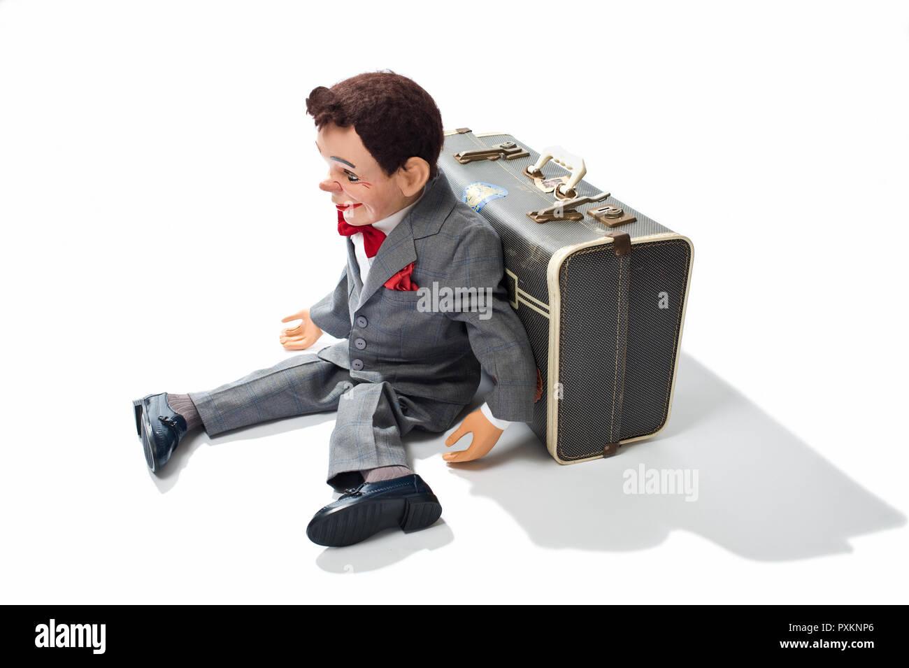 Un mannequin ventriloquiste assis contre une valise Banque D'Images