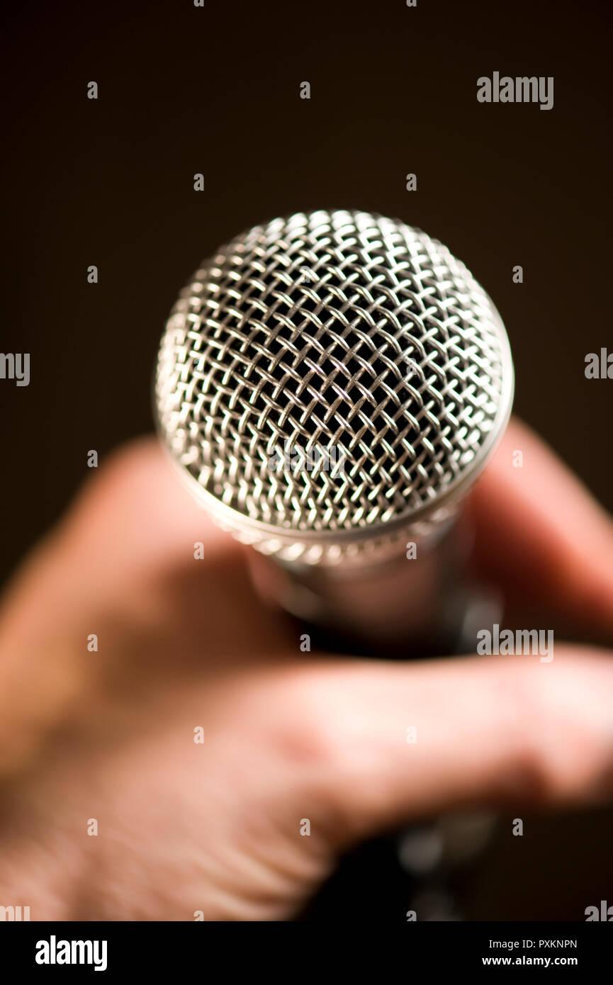 Une main tenant un microphone, gros plan Banque D'Images