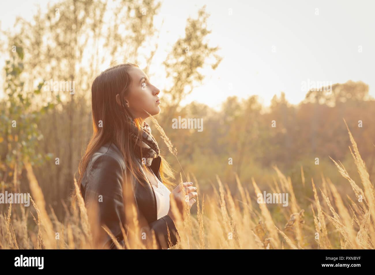 Belle jeune femme triste marche à l'herbe sèche, vue de profil Banque D'Images