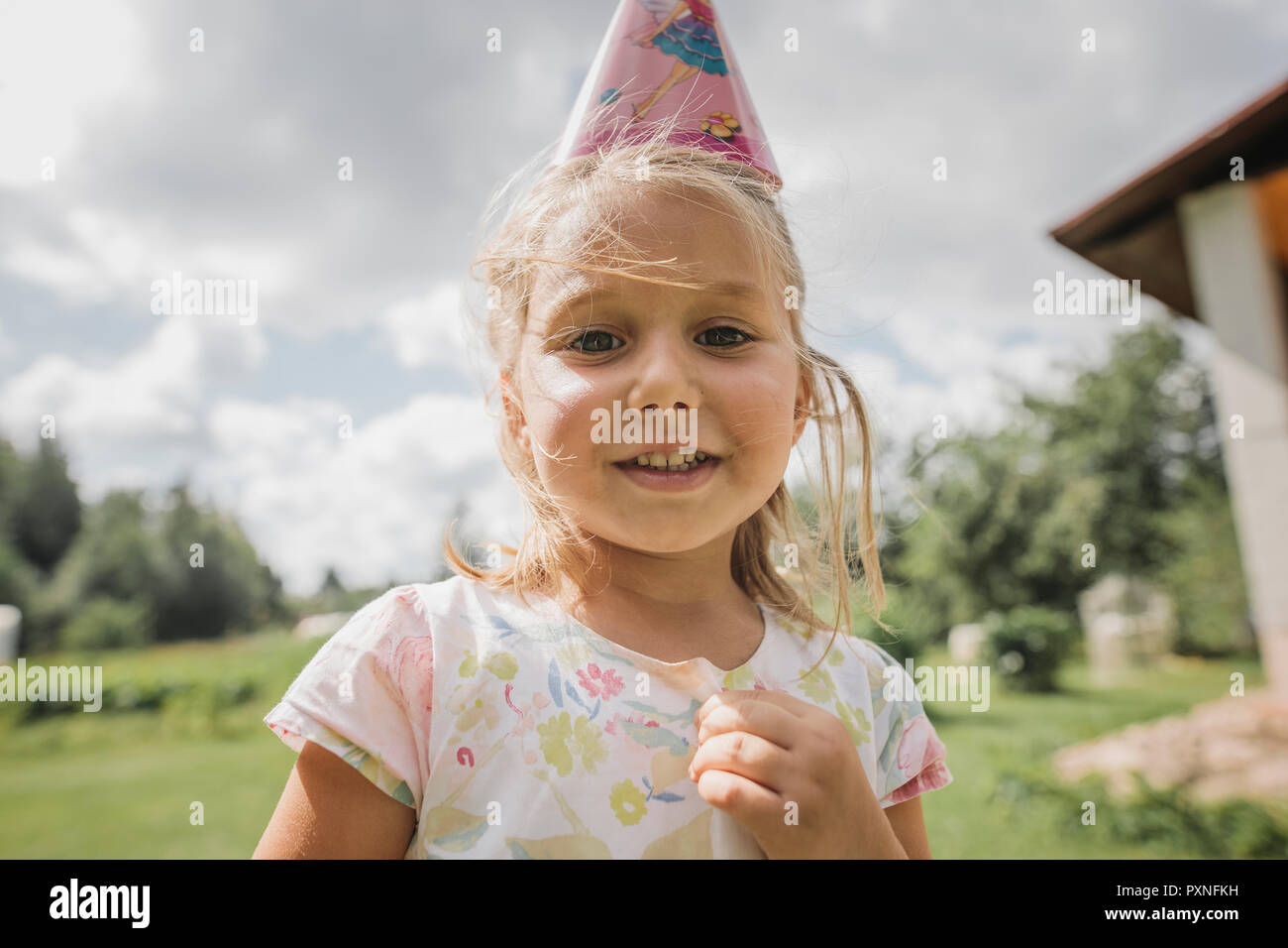 Portrait of smiling little girl wearing paper cone Banque D'Images