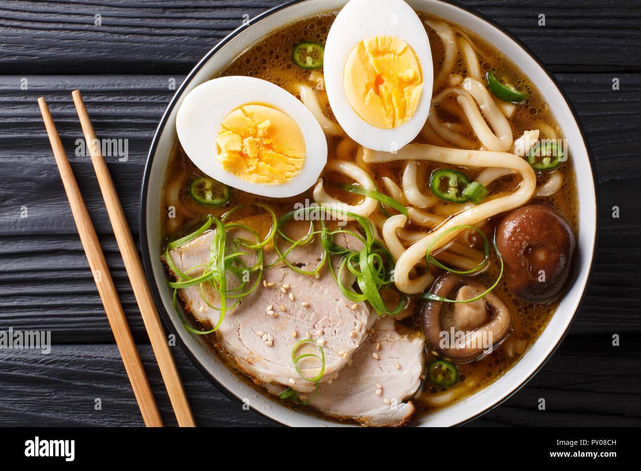 Soupe de nouilles Udon épicé, porc, œufs durs, oignons et champignons shiitake close-up dans un bol sur la table. haut horizontale Vue de dessus Photo Stock