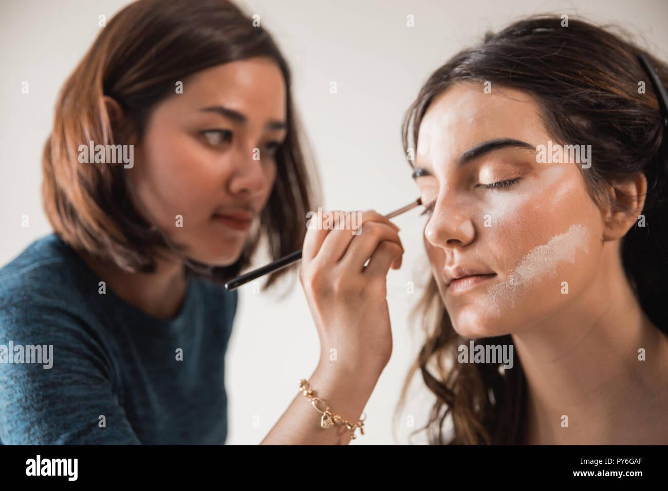 Jolie femme ayant le maquillage appliqué par un artiste de