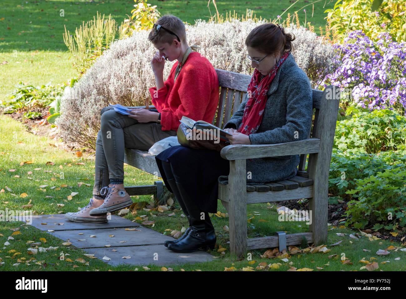 Deux jeunes femmes ou les femmes étudiants assis ou assis sur un banc en bois dans le jardin de l'évêque à la cathédrale de Chichester dans le West Sussex la lecture de livres. Banque D'Images