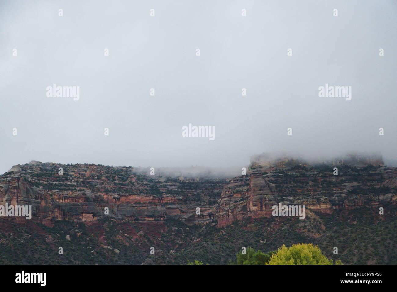 Le Colorado National Monument enveloppé d'une couche de brouillard. Les nuages au-dessus sont gris et sombre. Il y a une vibe baissés. Photo Stock