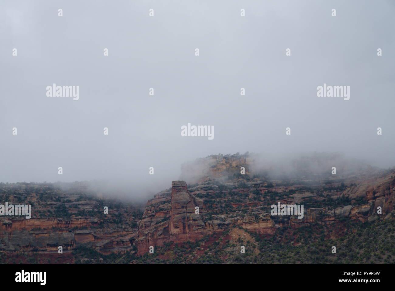 Le Colorado National Monument enveloppé d'une couche de brouillard. Les nuages au-dessus sont gris et sombre. Le ton général est abattu. Photo Stock