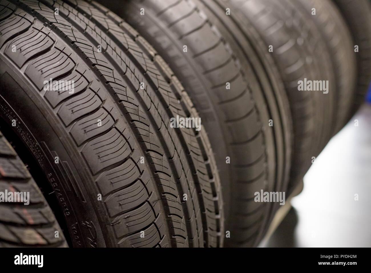 Nouveau pneu de voiture noire, gros plan.Tout nouveau pneus hiver avec une bande de roulement moderne.isolés selective focus.pile de pneus background.saison d'hiver. La texture de la bande de roulement des pneus de voiture. Banque D'Images