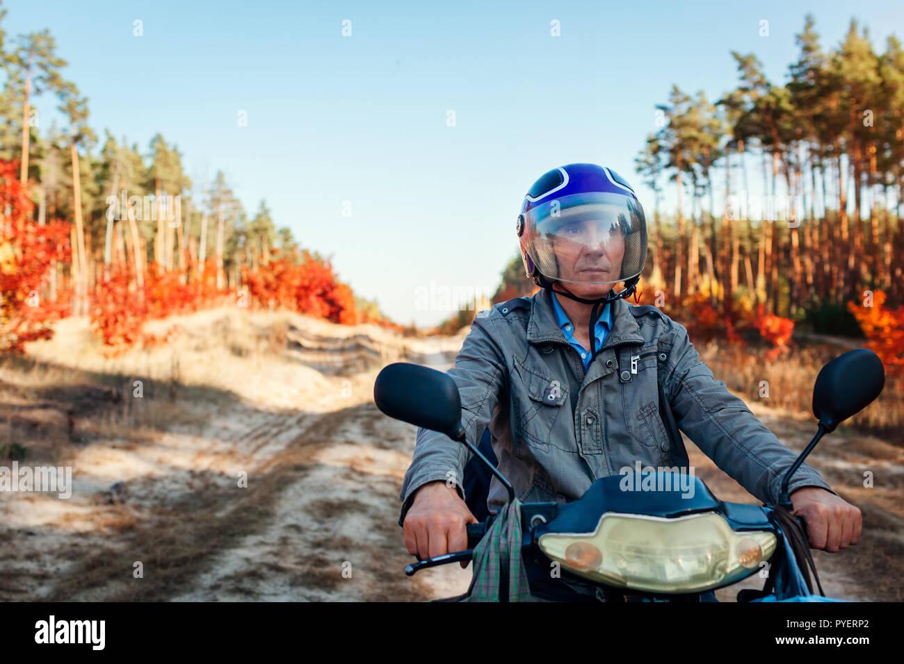 Senior man riding scooter sur la route forestière de l'automne. Conducteur en équitation casque scooter. Mode de vie actif Banque D'Images