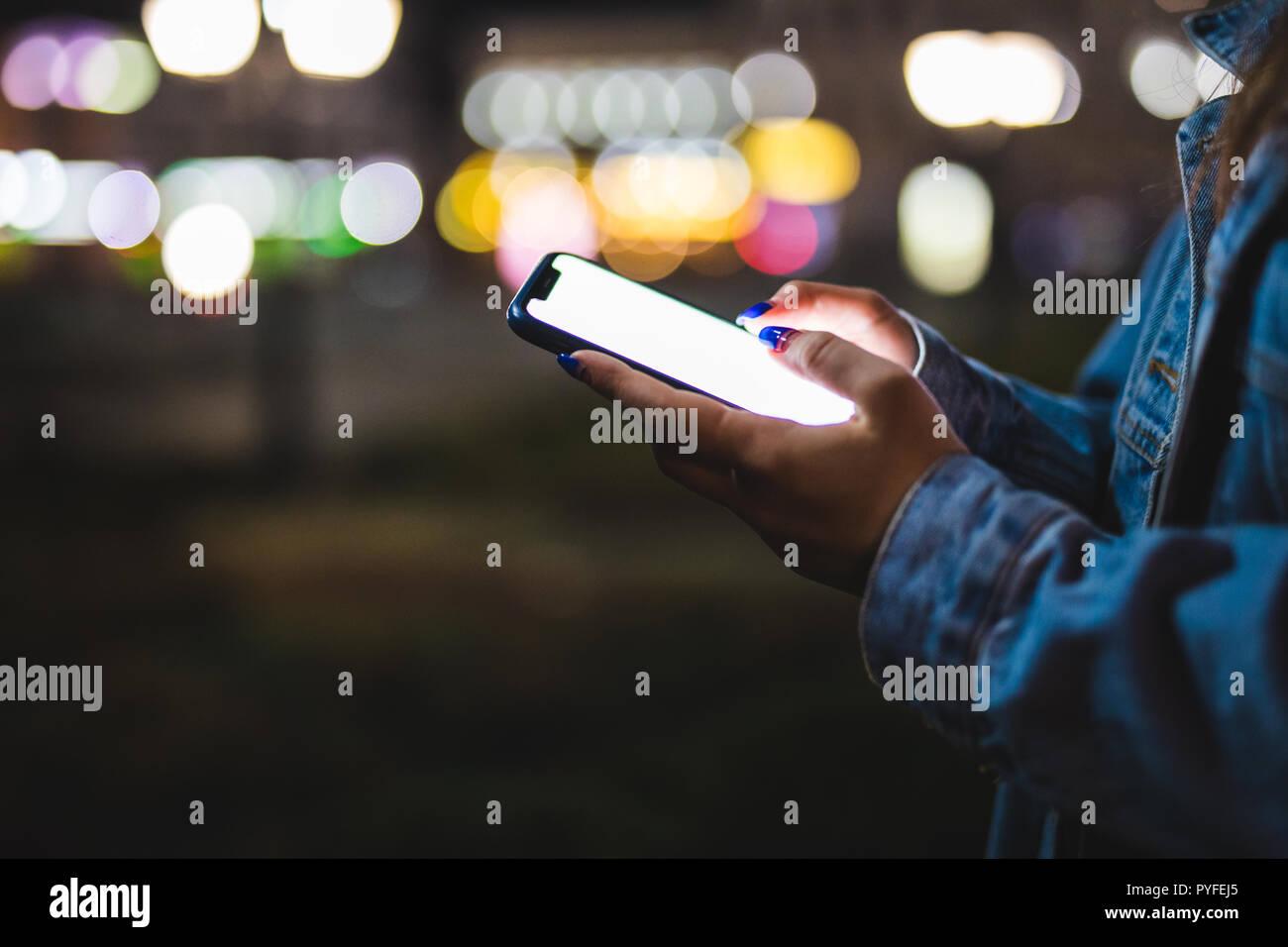 Femme doigt sur l'écran vierge du smartphone sur le flou d'arrière-plan de la lumière dans l'atmosphère de nuit, ville à l'aide dans les mains propres hipster gadget mobile phone Banque D'Images