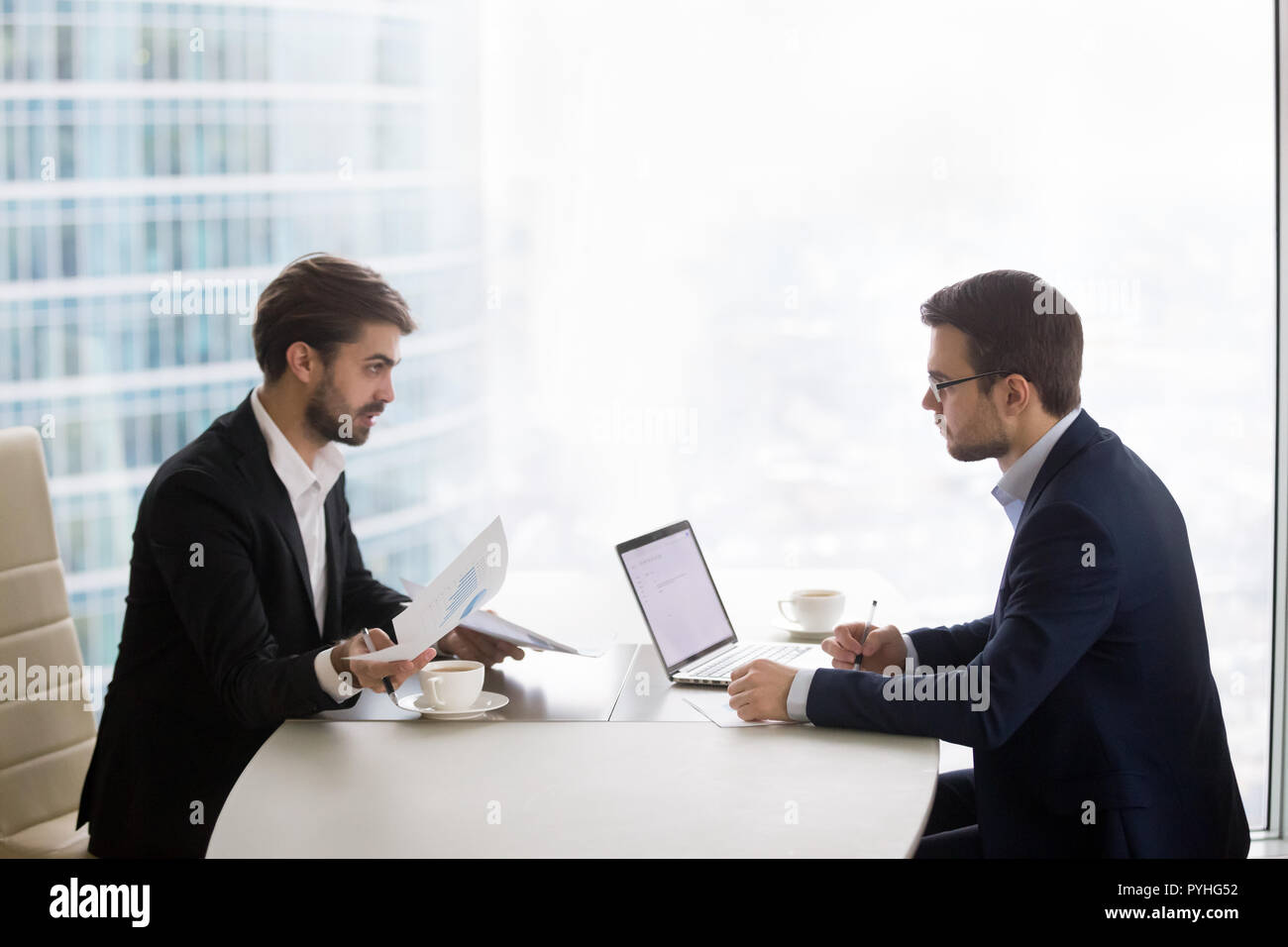 Deux hommes parlent et travaillent avec des papiers in office Photo Stock