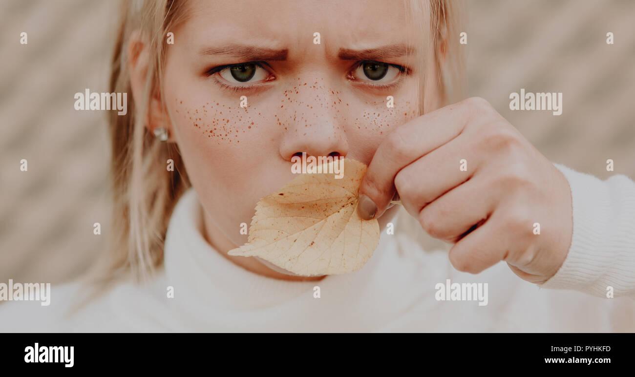 Jeune femme avec des taches de rousseur sur son visage les sourcils et se couvrir la bouche avec une feuille Banque D'Images