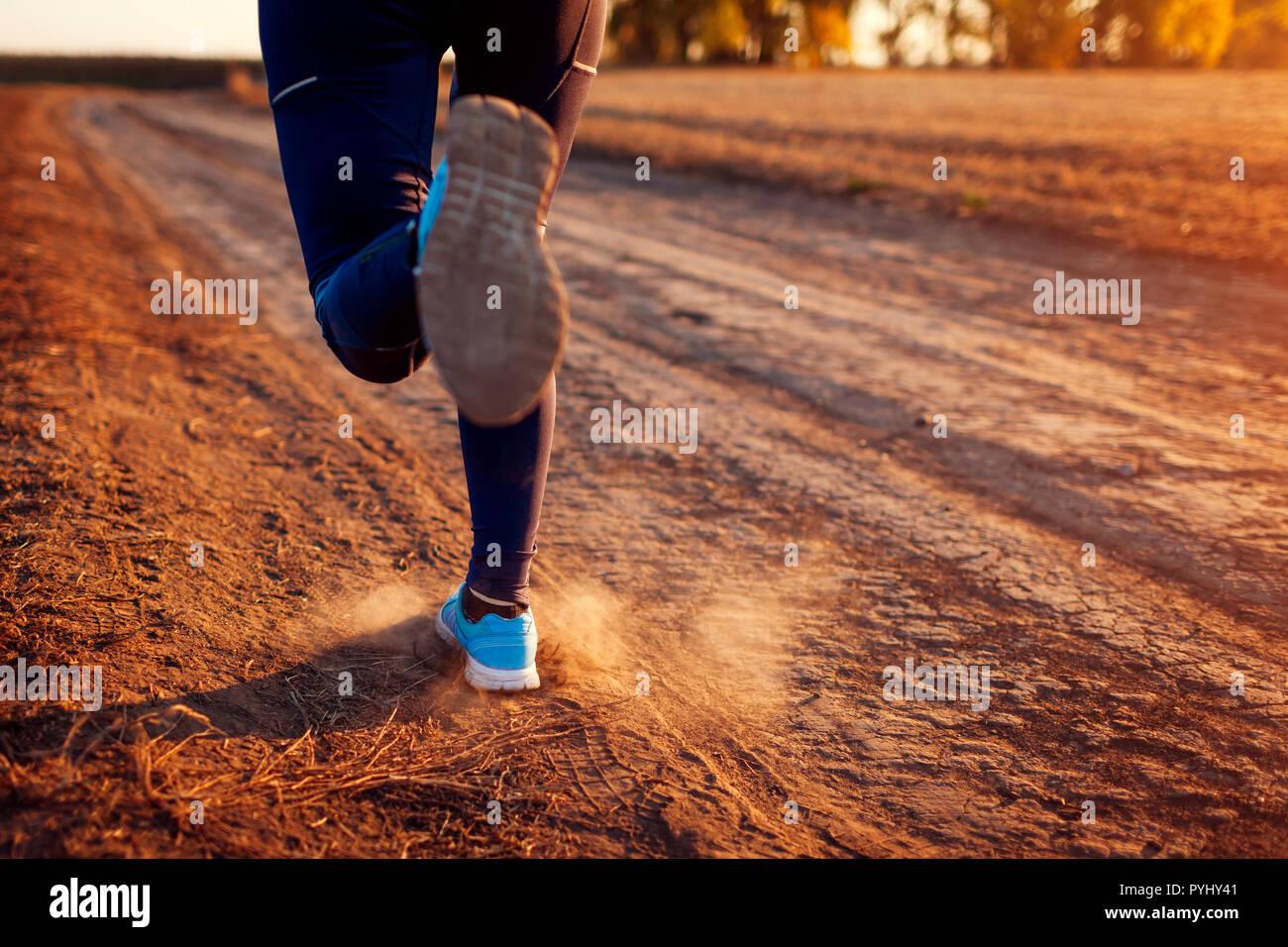 Femme d'exécution dans le champ d'automne au coucher du soleil. Concept de vie sain. Sportifs actifs. Close up de jambes Banque D'Images