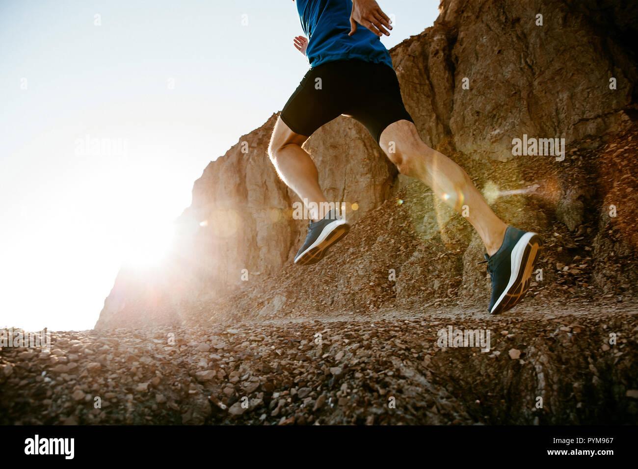 Homme d'âge moyen de vie sain runner s'exécutant sur sentier de montagne au coucher du soleil Banque D'Images