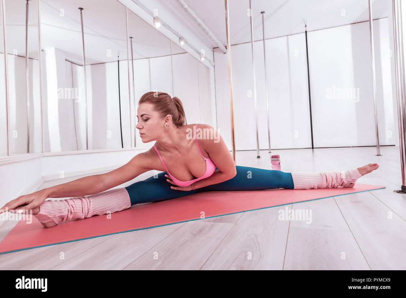 Femme fond du yoga partagé son jambes écartées tout en étirant son corps Photo Stock