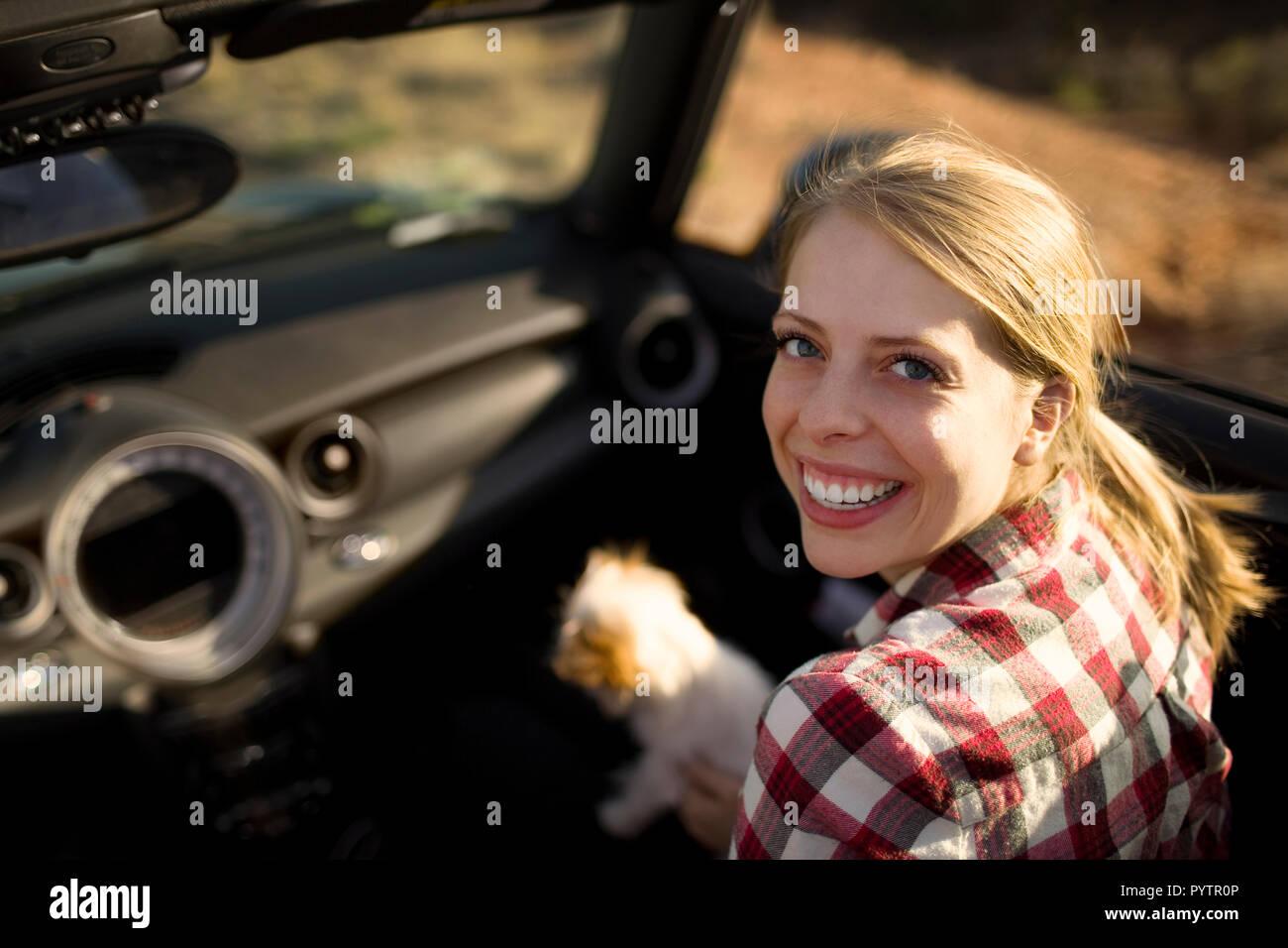 Portrait d'une jeune femme assise dans le siège passager d'une voiture décapotable avec son petit chien. Banque D'Images