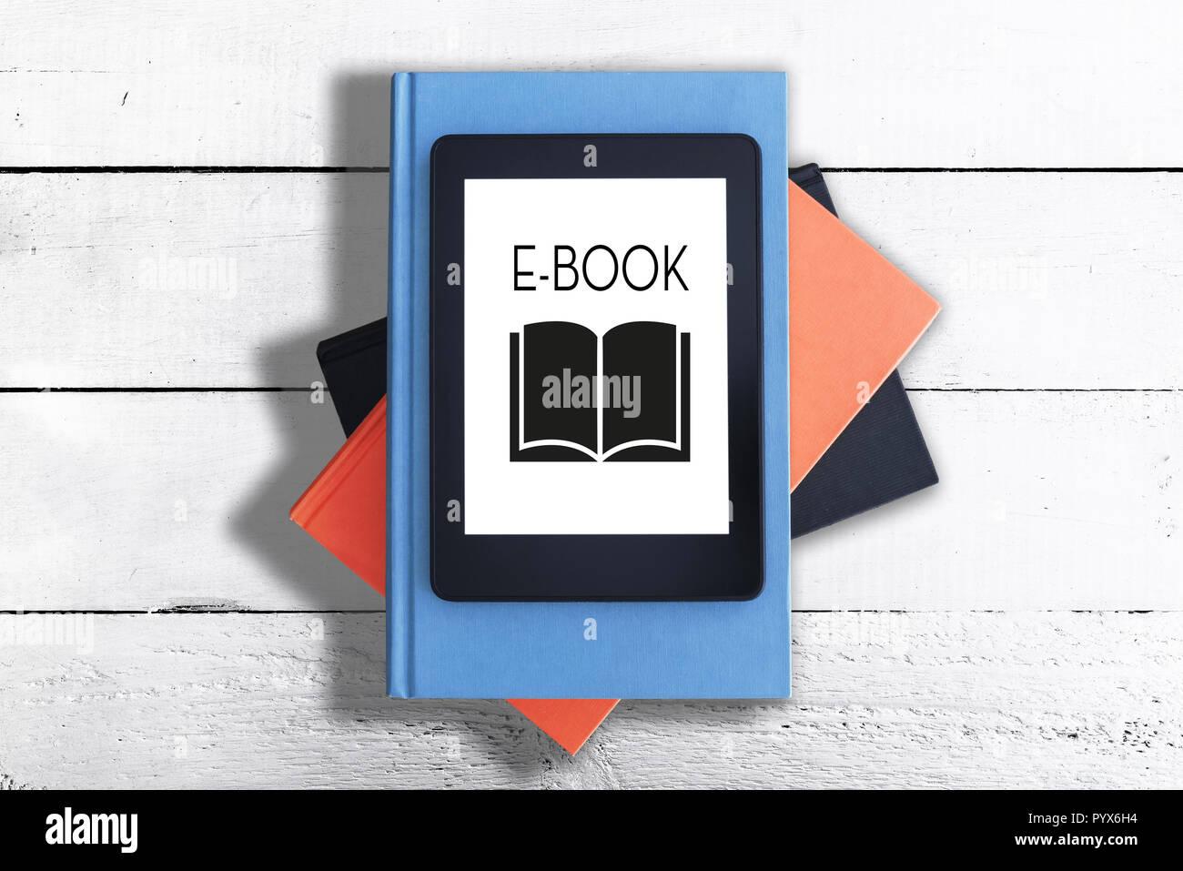 E-reader sur pile de livres contre table rustique en bois blanc Photo Stock