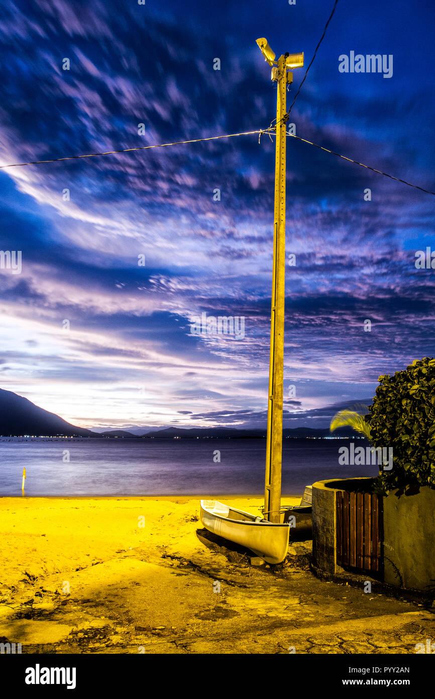Bateau amarré à un poteau d'éclairage à Ribeirao da Ilha Plage au crépuscule. Florianopolis, Santa Catarina, Brésil Photo Stock
