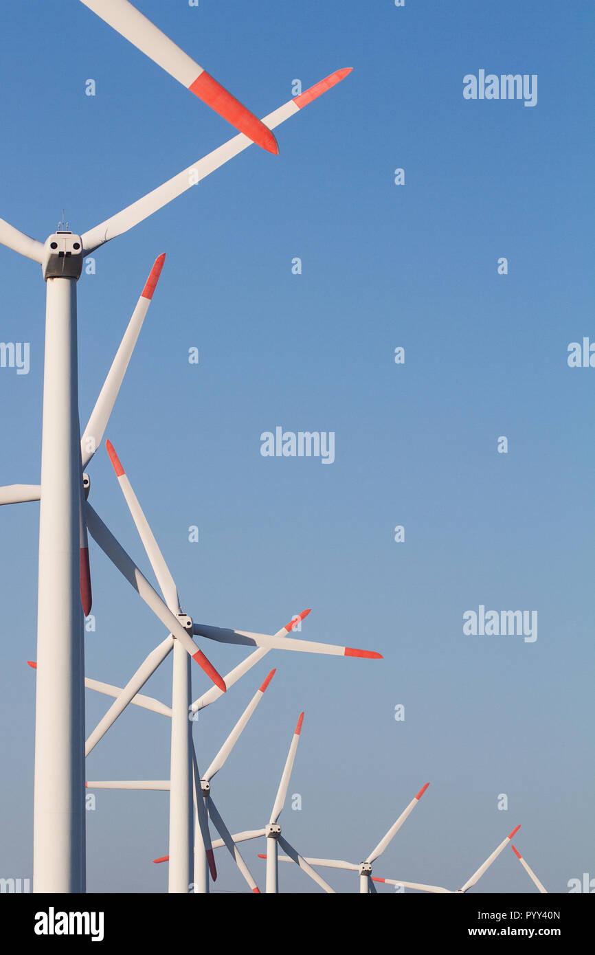 Vue avant de la rangée verticale éolienne éoliennes blanches dans une ferme de l'énergie contre un ciel bleu clair avec copyspace Banque D'Images