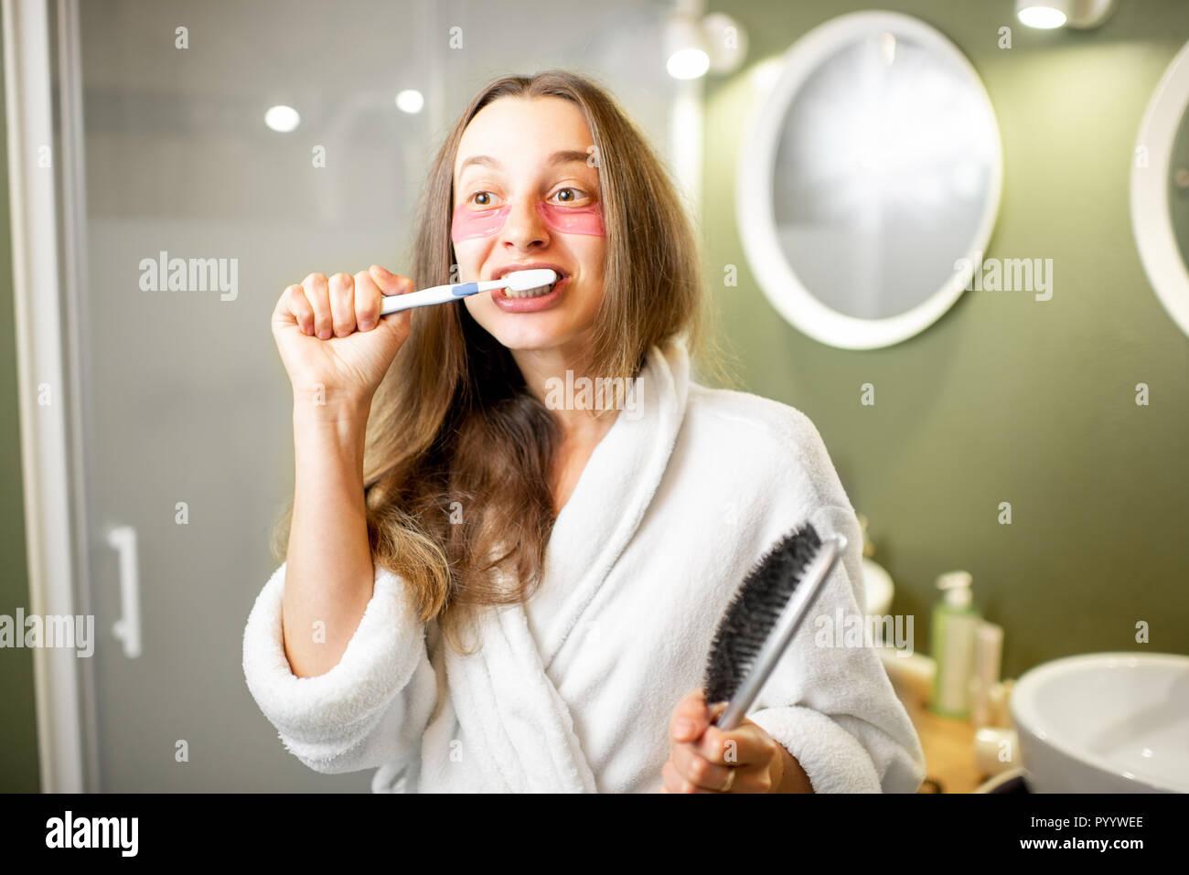 Jeune et belle femme en peignoir se brosser les dents dans la salle de bains Banque D'Images